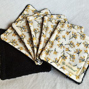 Carrés démaquillants tissu à motif branches fleuries noires, grises, ocre et jaunes sur fond blanc et tissu éponge noir coton bio