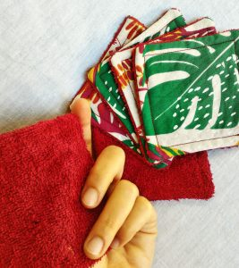 Lot de coton démaquillants vert orange rouge et bordeau avec des motifs de feuilles monstera sur fond blanc cassé