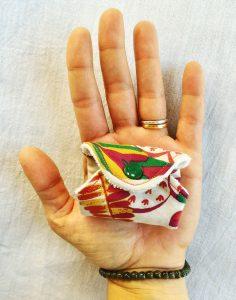 Protège slip lavable replié sur lui même dans une main motif feuilles et plantes oranges rouges vertes et bordeaux sur fond blanc cassé
