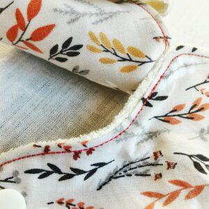 Détail de deux protège slips lavables motif feuilles, branches et graminé oranges, jaunes, ocre gris et noirs sur fond rose pale