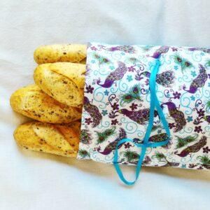 sac à pain motif paons violet vert anis et bleu sur fond blanc et quatre baguettes aux céréales